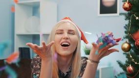 Jovem mulher bonita no chapéu de Santa que funde confetes coloridos na câmera filme