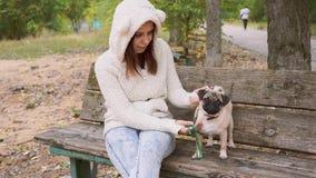 Jovem mulher bonita no parque que senta-se no banco video estoque