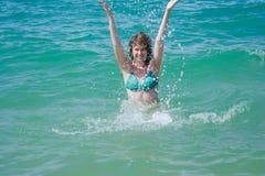 Jovem mulher bonita no pulverizador do mar imagens de stock