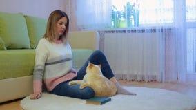 A jovem mulher bonita no revestimento e em calças de brim cor-de-rosa brancos delicados senta-se no tapete bege redondo no gato v filme