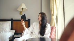Jovem mulher bonita no roupão que conversa no tablet pc que senta-se na cadeira na sala de hotel video estoque