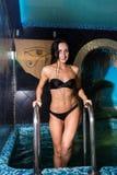 Jovem mulher bonita no roupa de banho do biquini que aumenta em cima na piscina imagem de stock royalty free