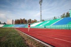 Jovem mulher bonita no short cor-de-rosa e no tanque para exercitar movimentar-se e correr na trilha atlética no estádio no nasce imagens de stock