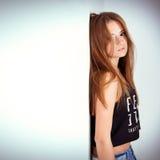 A jovem mulher bonita no short da sarja de Nimes está no estúdio no fundo branco-azul Imagem de Stock