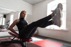 A jovem mulher bonita no sportswear à moda preto nas sapatilhas brancas senta-se no simulador e executa-se exercícios imagem de stock