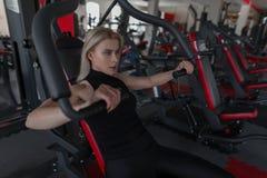A jovem mulher bonita no sportswear preto é contratada no assento no simulador em um estúdio da aptidão fotografia de stock royalty free