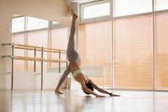 Jovem mulher bonita no sportswear que executa a pose difícil da ioga no assoalho no estúdio claro imagem de stock