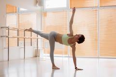 Jovem mulher bonita no sportswear que executa a pose difícil da ioga no assoalho no estúdio claro fotografia de stock