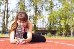 Jovem mulher bonita no sutiã dos esportes que estica a limitação em Trac Fotos de Stock Royalty Free