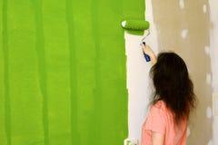 A jovem mulher bonita no t-shirt cor-de-rosa está pintando entusiasticamente a parede interior verde com rolo em uma casa nova imagem de stock royalty free