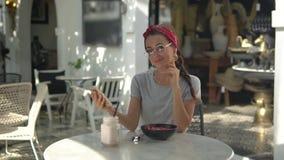 Jovem mulher bonita no t-shirt que senta-se no café e na conversa filme