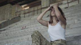 Jovem mulher bonita no uniforme militar que senta-se nas escadas concretas frias na construção abandonada A menina filme