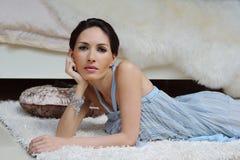 Jovem mulher bonita no vestido azul que descansa em um assoalho no interior refinado fotos de stock