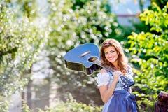 Jovem mulher bonita no vestido bávaro tradicional que guarda o guit foto de stock royalty free