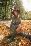 Jovem mulher bonita no vestido cinzento da malha que senta-se no parque no aut Imagem de Stock Royalty Free