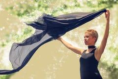 Jovem mulher bonita no vestido de noite preto que guarda a tela preta no vento Fotos de Stock