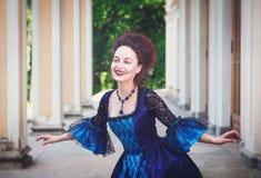 Jovem mulher bonita no vestido medieval azul que faz o curtsey Imagens de Stock