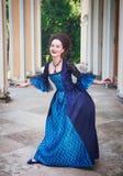 Jovem mulher bonita no vestido medieval azul que faz o curtsey Fotos de Stock Royalty Free