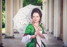 Jovem mulher bonita no vestido medieval verde com guarda-chuva Fotografia de Stock