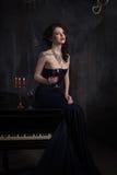 Jovem mulher bonita no vestido preto ao lado de um piano com velas dos candelabros e vinho, atmosfera dramática escura do castelo foto de stock