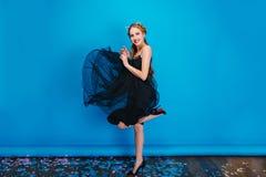 Jovem mulher bonita no vestido preto de vibração, levantando no fundo azul, dançando no partido Tem o cabelo louro, vestindo fotos de stock royalty free