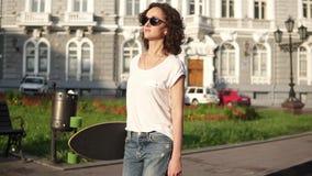 Jovem mulher bonita nos óculos de sol que anda na rua velha da cidade que guarda seu longboard na manhã durante o alvorecer filme