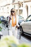 jovem mulher bonita nos óculos de sol que guardam o copo de café descartável e que usam o smartphone ao andar fotografia de stock