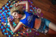 A jovem mulher bonita nos fones de ouvido tem o divertimento e escuta música fotos de stock