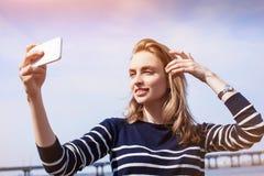 A jovem mulher bonita, o louro, fazendo o selfie que usa fora o smartphone e a conexão a Internet 4G rápida ao estar contra rive Fotografia de Stock Royalty Free