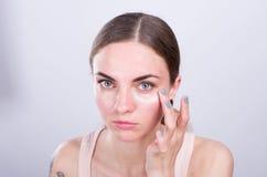 A jovem mulher bonita põe o creme sobre sua cara Imagens de Stock Royalty Free