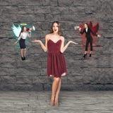 A jovem mulher bonita pensa, um anjo e um diabo foto de stock royalty free