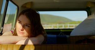 Jovem mulher bonita pensativa que olha afastado ao sentar-se em camionete 4k video estoque