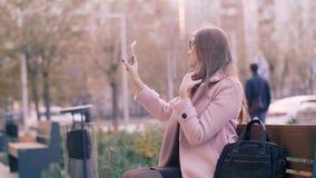 Jovem mulher bonita que ajusta o cabelo longo ao tomar o selfie no smartphone fora filme