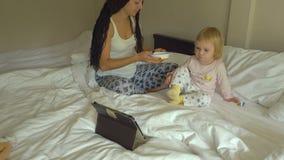 Jovem mulher bonita que alimenta o papa de aveia pequeno do bebê ao olhar no tablet pc filme