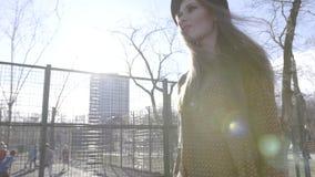 Jovem mulher bonita que anda ao longo da rua no dia ensolarado a??o Jovem mulher elegante que anda ao longo da cerca vídeos de arquivo