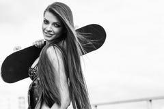 Jovem mulher bonita que anda e que guarda um skate Imagem de Stock Royalty Free