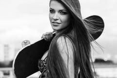 Jovem mulher bonita que anda e que guarda um skate Fotografia de Stock