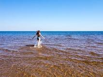 Jovem mulher bonita que anda na água fotos de stock royalty free