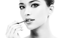 Jovem mulher bonita que aplica a composição dos bordos com escova cosmética Foto de Stock Royalty Free