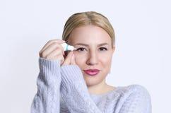 Jovem mulher bonita que aplica gotas de olho Imagem de Stock