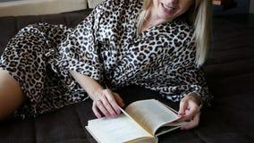 Jovem mulher bonita que aprecia lendo um livro em casa que encontra-se na cama que sorri no prazer no vestido de molho filme
