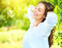 Jovem mulher bonita que aprecia a natureza exterior Menina moreno de sorriso feliz que relaxa no parque do verão imagem de stock royalty free