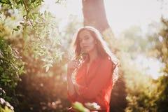 Jovem mulher bonita que aprecia o por do sol fotografia de stock royalty free