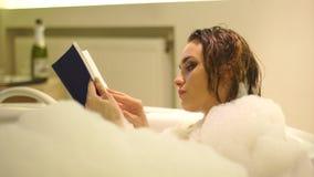 Jovem mulher bonita que banha e que lê um livro na banheira de hidromassagem com espuma filme
