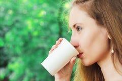 Jovem mulher bonita que bebe o café afastado Imagem de Stock