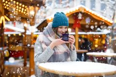 Jovem mulher bonita que bebe o perfurador quente, vinho ferventado com especiarias no mercado alemão do Natal Menina feliz na rou foto de stock royalty free