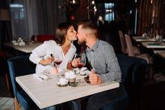 Jovem mulher bonita que beija seu nariz do ` s do homem em um restaurante imagens de stock royalty free