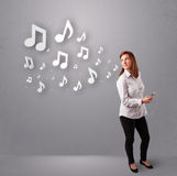 Jovem mulher bonita que canta e que escuta a música com n musical Foto de Stock Royalty Free