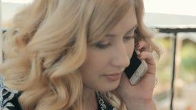 Jovem mulher bonita que chama o telefone e que fala em um café no terraço do verão vídeos de arquivo