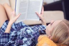 Jovem mulher bonita que coloca no assoalho em casa, lendo um livro, interior da sala de visitas Menina que lê um livro no fotos de stock royalty free